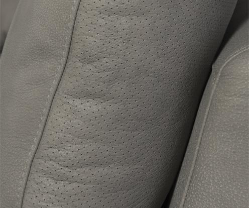 Zbliżenie na dekoracyjne przeszycia i perforacje szarej skóry  narożnika Figaro Due marki Kler