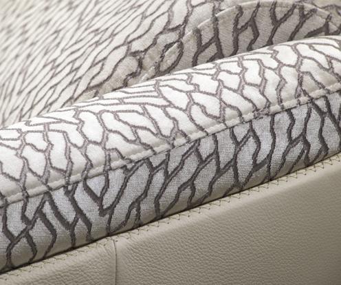 Zbliżenie na dekoracyjne przeszycia i łączenie tkaniny ze skórą na podłokietniku sofy Kler Gondoliere.