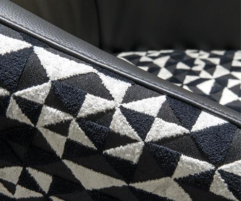 Zbliżenie na podłokietnik fotela Cornetta z oferty Kler z pokazaniem ozdobnego przeszycia w miejscu łączenia skóry i tkaniny.