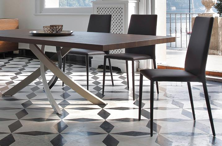 Stół Artistico z oferty Kler firmy Bontempi, w towarzystwie krzeseł. Stół z drewnianym, ciemnym blatem na nowoczesnej jasnej podstawie.