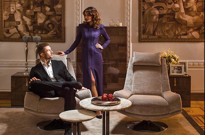 Dwoje ludzi w salonie zaaranżowanym beżowymi fotelami Kler Andante oraz brązowymi komodami.