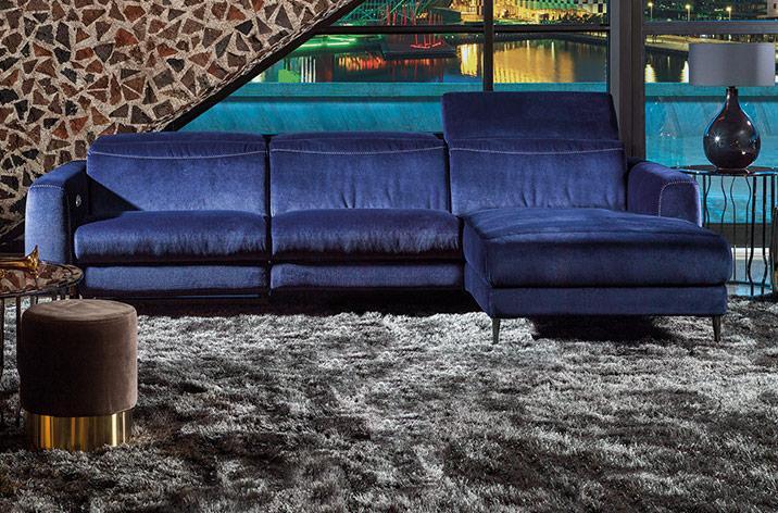 Narożnik Kler Capriccio w niebieskiej tkaninie z rozłożonym zagłówkiem w nowoczesnym salonie.