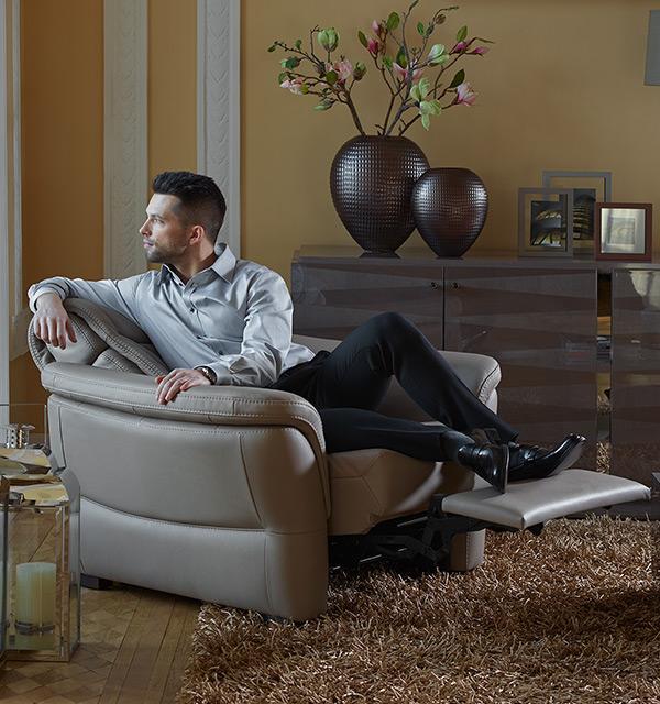 Mężczyzna siedzący w fotelu Kler Fantasia w szarej skórze