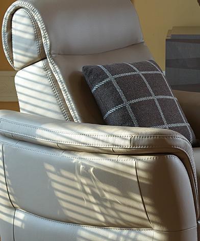 Dekoracyjne przeszycia podłokietnika w fotelu Kler Fantasia. Dekoracyjny szew na beżowej skórze.