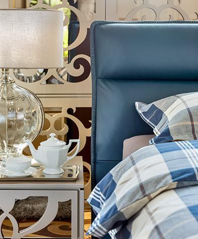 Detal na tapicerowane wezgłowie łóżka Balletto firmy Kler w niebieskiej skórze oraz stolik nocny Ornamento firmy Kler.