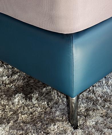 Detal nogi łóżka Balletto firmy Kler tapicerowanego skórą w kolorze niebieskim.