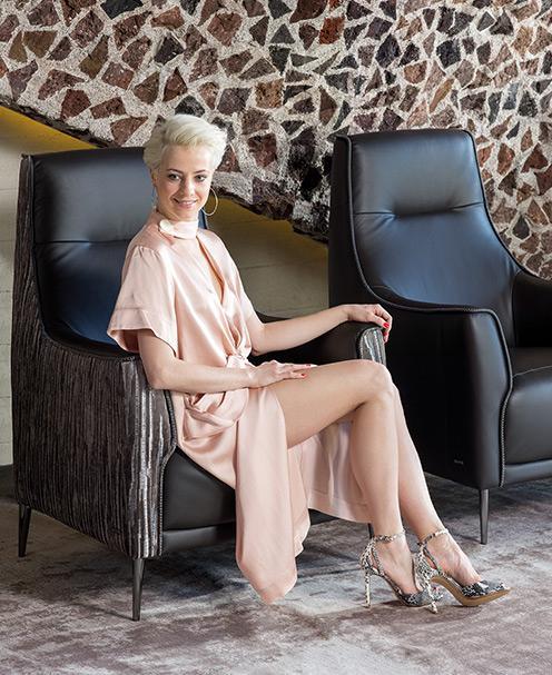 Wygodny fotel Kler Alto w czarnej skórze z podłokietnikiem wykonanym z tkaniny i chromowanymi nóżkami.