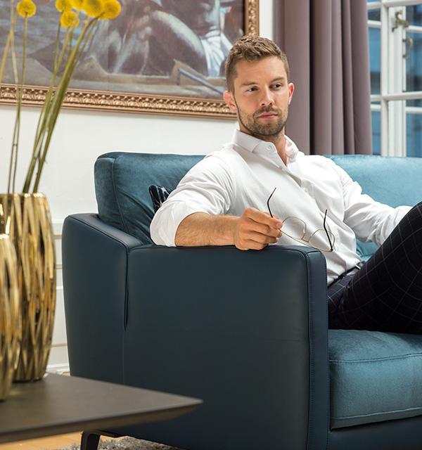 Mężczyzna w białej koszuli siedzący na niebieskiej sofie Diva firmy Kler