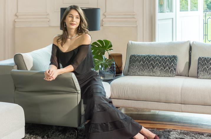 Kobieta siedząca na narożniku Kler Concerto w szarym obiciu, na meblu leżą ciemno-szare poduszki.