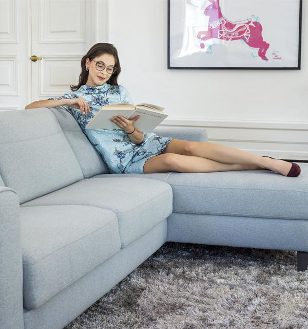 Kobieta czytająca książkę na sofie Kler Bolero w niebieskiej tkaninie