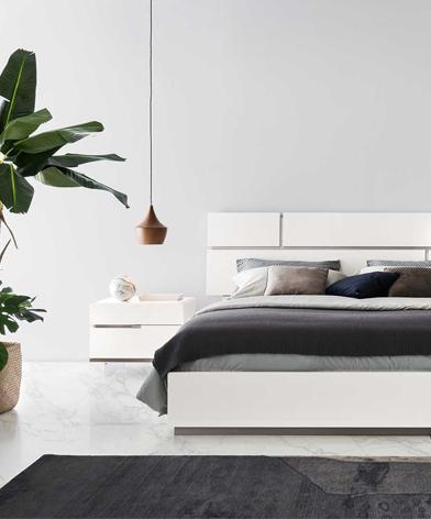 Fragment łóżka wraz ze stolikiem nocnym  z kolekcji Artemide z oferty Kler w kolorze białym.