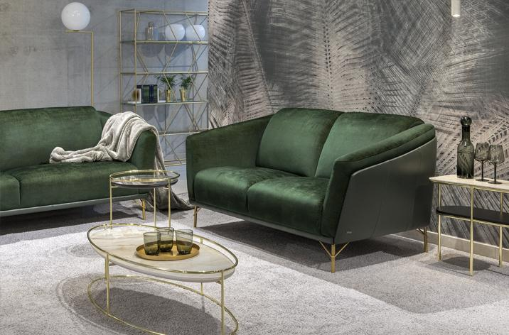 Wykonana w połączeniu zielonej skóry i tkaniny sofa Gondoliere firmy Kler ze złotymi nóżkami. Obok kolekcja stolików w kolorze złotym z kamiennymi blatami.
