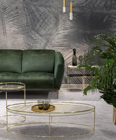 Fragment zielonej sofy Gondoliere marki Kler, stojącej obok złotego stolika z kamiennym blatem.