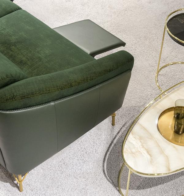 Widok z góry na podłokietnik sofy Gondoliere firmy Kler, pokazujący łączenie zielonej skóry i tkaniny