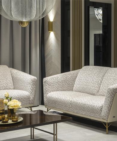 Sofa Gondoliere marki Kler, umieszczona w eleganckim salonie przy stoliku kawowym z brązowym blatem i złotymi nóżkami.