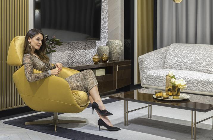 Kobieta siedząca w wygodnym, nowoczesnym fotelu Kler Cornetta w złotym obiciu, umieszczonym w eleganckim salonie