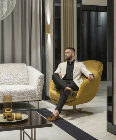 Mężczyzna w marynarce siedzący w wygodnym fotelu Cornetta marki Kler, w złotym kolorze.