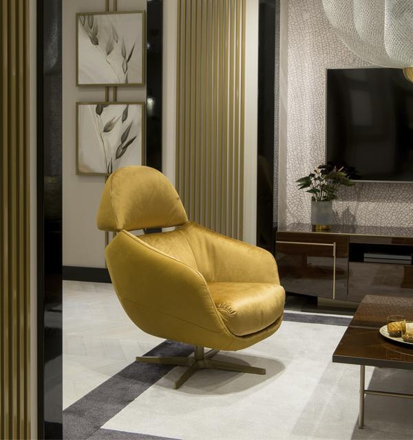 Złoty fotel Kler Cornetta o owalnym kształcie w eleganckim salonie