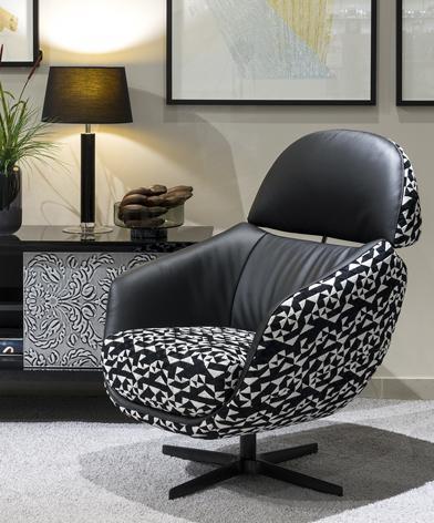Wykonany z tkaniny i skóry, czarno-biały fotel Kler Cornetta z prostą czarną podstawą umieszczony w salonie.