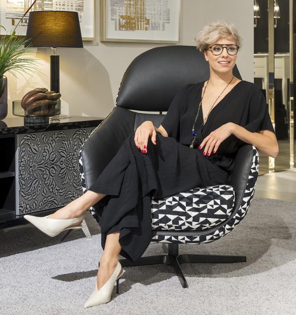 Kobieta w czarnej sukience i w okularach, siedząca w fotelu Kler Cornetta z czarną podstawą