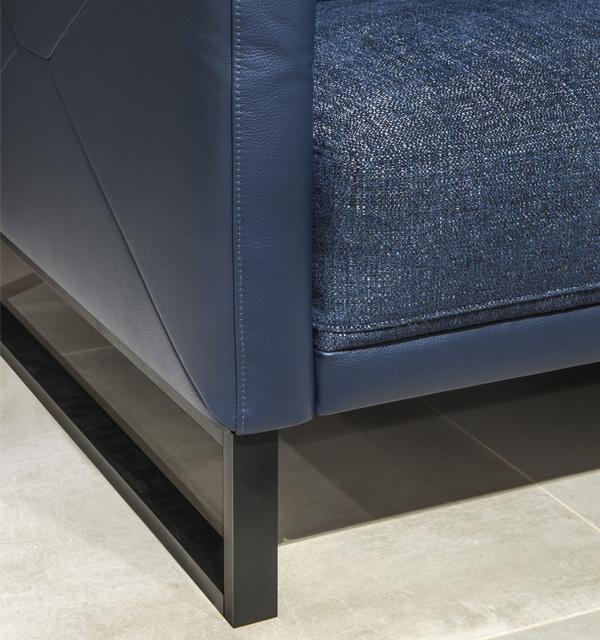 Zbliżenie na metalową, czarną płozę fotela Kler Estrada w niebieskiej skórze
