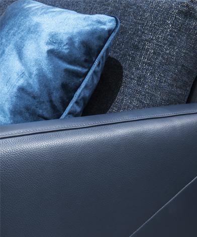 Zbliżenie na dekoracyjne przeszycie podłokietnika fotela z kolekcji Kler Estrada w niebieskiej skórze.