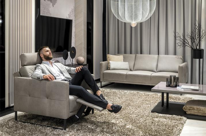 Mężczyzna siedzący w wygodnym, rozłożonym, szarym fotelu Kler Estrada z metalową czarną płozą.