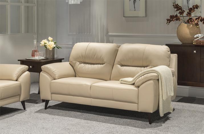 Beżowe, skórzane obicie, brązowe, drewniane nóżki, - sofa Kler Bartolo w eleganckim salonie.