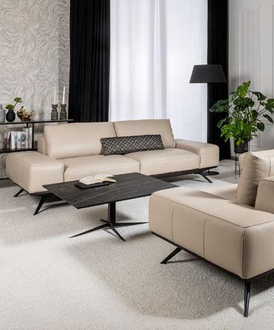 Elegancki  salon wyposażony w sofę Figaro Uno z oferty marki Kler. Beżowa skóra, czarne eleganckie nóżki sofy korespondują ze stojącym obok stolikiem z kamiennym blatem.