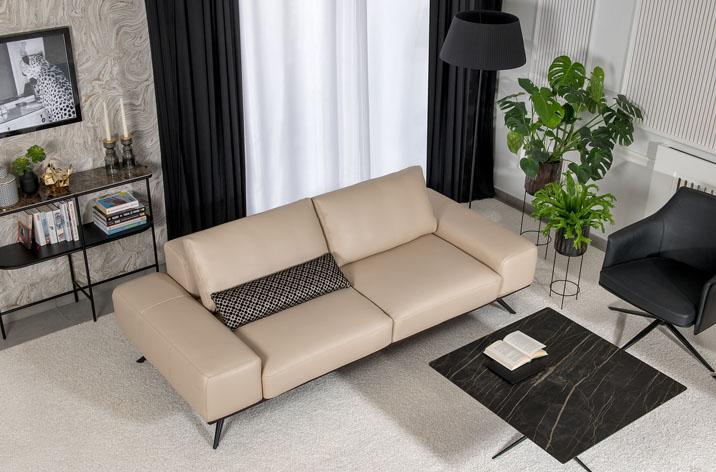 Widok z góry na sofę Kler Figaro Uno w beżowej skórze,obok kamienny prostokątny stolik, czarny fotel i lampa.