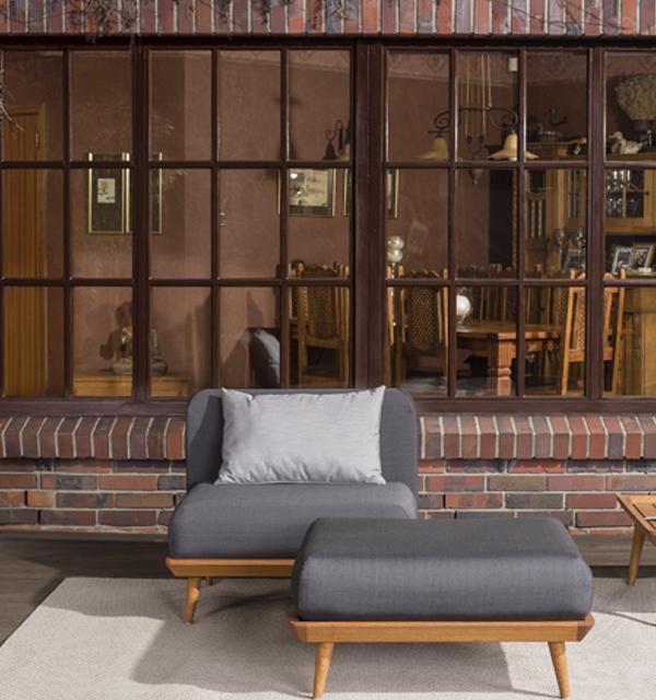Fotel i taboret ogrodowy z kolekcji Nourd dostępnej w salonach Kler. Elementy kolekcji wykonane z drewna w szarym obiciu.