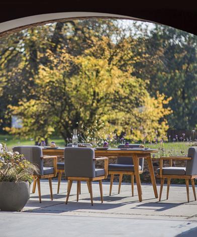 Komfortowy zestaw mebli ogrodowych Kler Bouhus w szarym obiciu na tarasie na tle ogrodu.