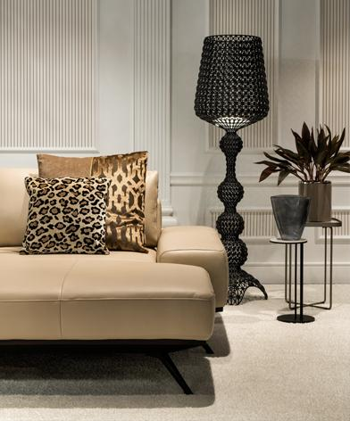 Fragment narożnika Figaro Uno Kler. Narożnik soi na jasnym dywanie, na wypoczynku ozdobne poduszki w zwierzęce wzory, w le nowoczesna lampa.