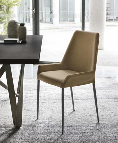 Musztardowe krzesło Havana z oferty Kler na metalowych nogach. Krzesło na jasnej wykładzinie, w towarzystwie stołu Wave z dekoracjami, w tle duże okno.
