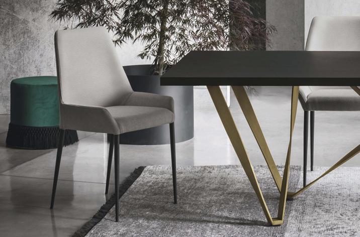 Zbliżenie na szare krzesło z kolekcji Wave z oferty Kler. Za krzesłem donica z rośliną i butelkowo-zielona pufa. Tuż obok krzesła fragment stołu Wave również z oferty Kler.
