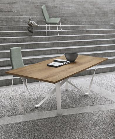 Zdjęcie aranżacyjne stołu Wave z oferty Kler, z jasnym drewnianym blatem, na białej podstawie. Oprócz stołu na zdjęciu znajdują się miętowe krzesła, a w tle betonowe schody.