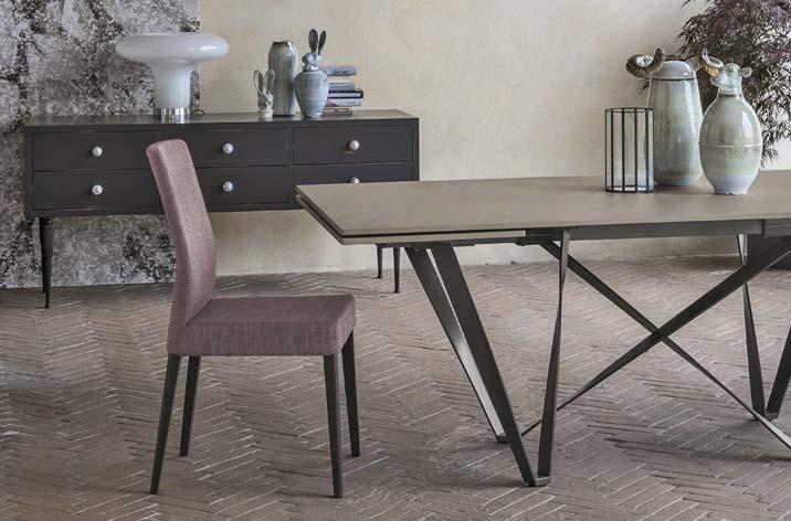 Fragment stołu Wave z oferty Kler. Stół stoi w nowoczesnej przzestrzeni w towarzystwie różowego krzesła, w tle komoda z dekoracjami.