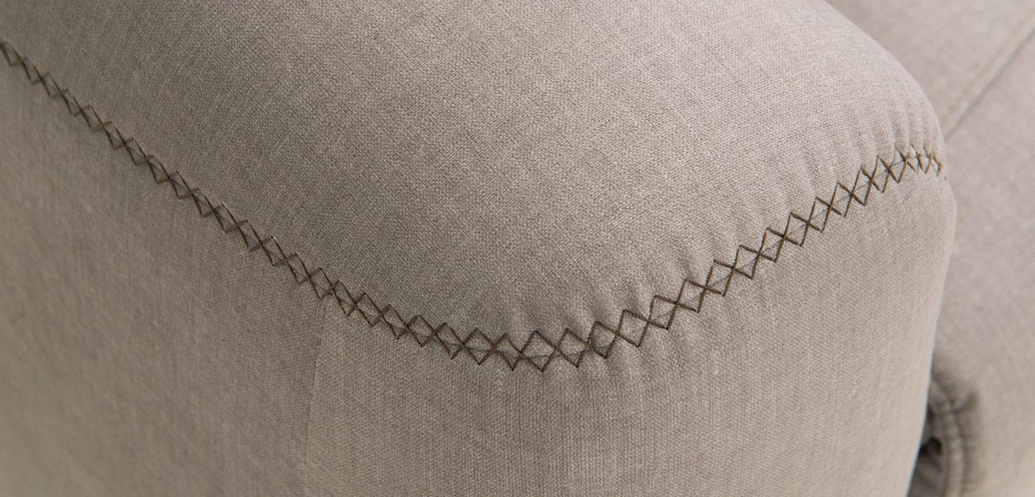 Zbliżenie na dekoracyjne przeszycie podłokietnika sofy Kler w tkaninie