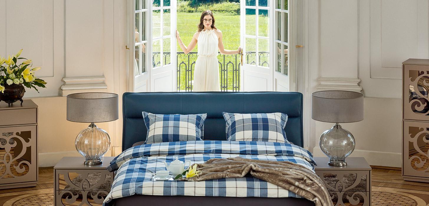Kontynentalne łóżko Balletto firmy Kler tapicerowane skórą w kolorze niebieskim, z imponującym wezgłowiem w towarzystwie stolików nocnych Ornamento firmy Kler.