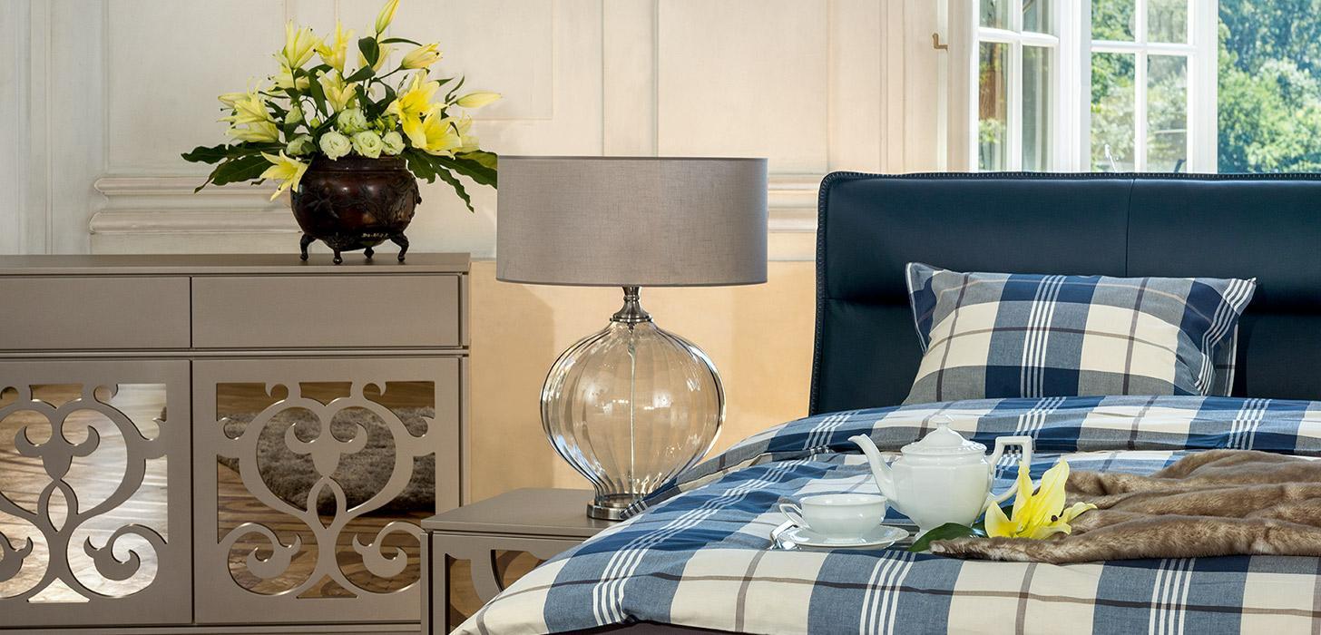 Zbliżenie na fragment łóżka Balletto firmy Kler, tapicerowanego niebieską skórą oraz na komodą i stolik nocny w kolorze beżowym z lustrzanymi wstawkami z kolekcji Ornamento firmy Kler.