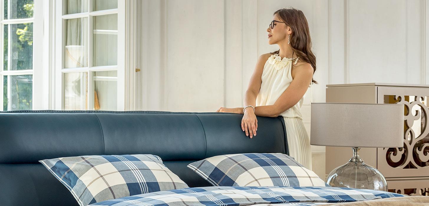 Kobieta oparta o imponujące wezgłowie łóżka Balletto firmy Kler, tapicerowane skórą w kolorze niebieskim. W tle komoda Ornamento firmy Kler z lustrzanymi wstawkami.
