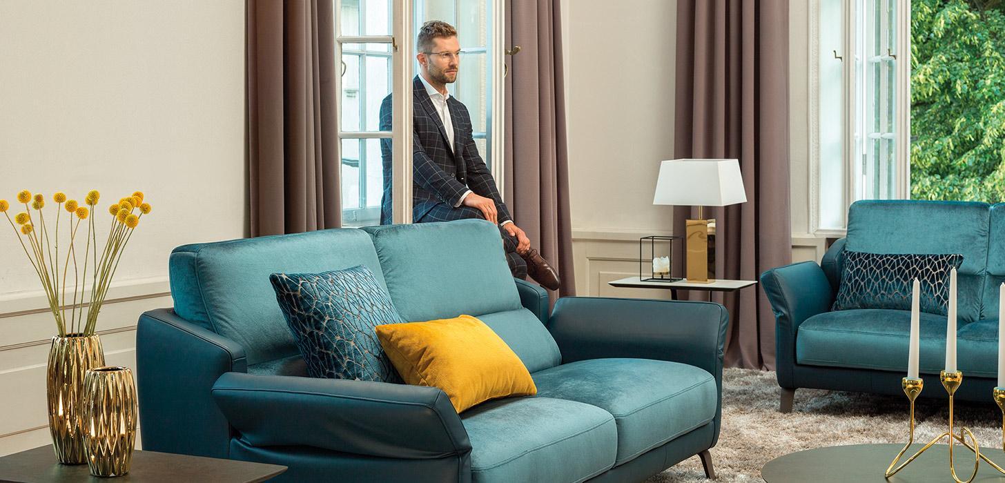 Fragment salonu z dwoma niebieskimi sofami Diva marki Kler , na meblu niebieskie i żółte poduszki