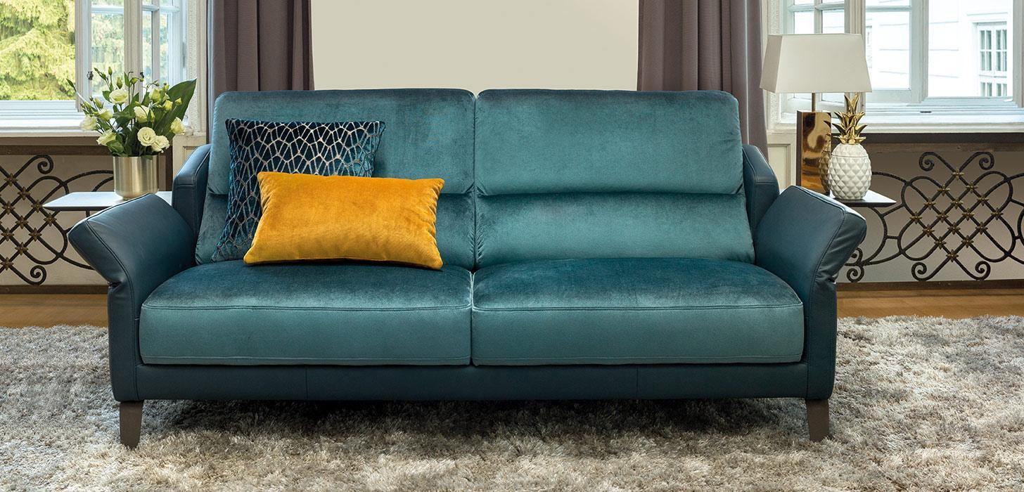 Niebieska sofa 3-osobowa Diva marki Kler z rozkładanymi podłokietnikami umieszczona w salonie