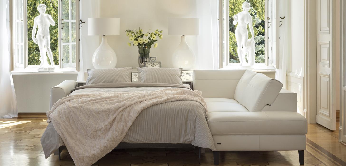 Narożnik Kler Bolero w białej skórze z rozłożonym łóżkiem, poduszkami i pościelą