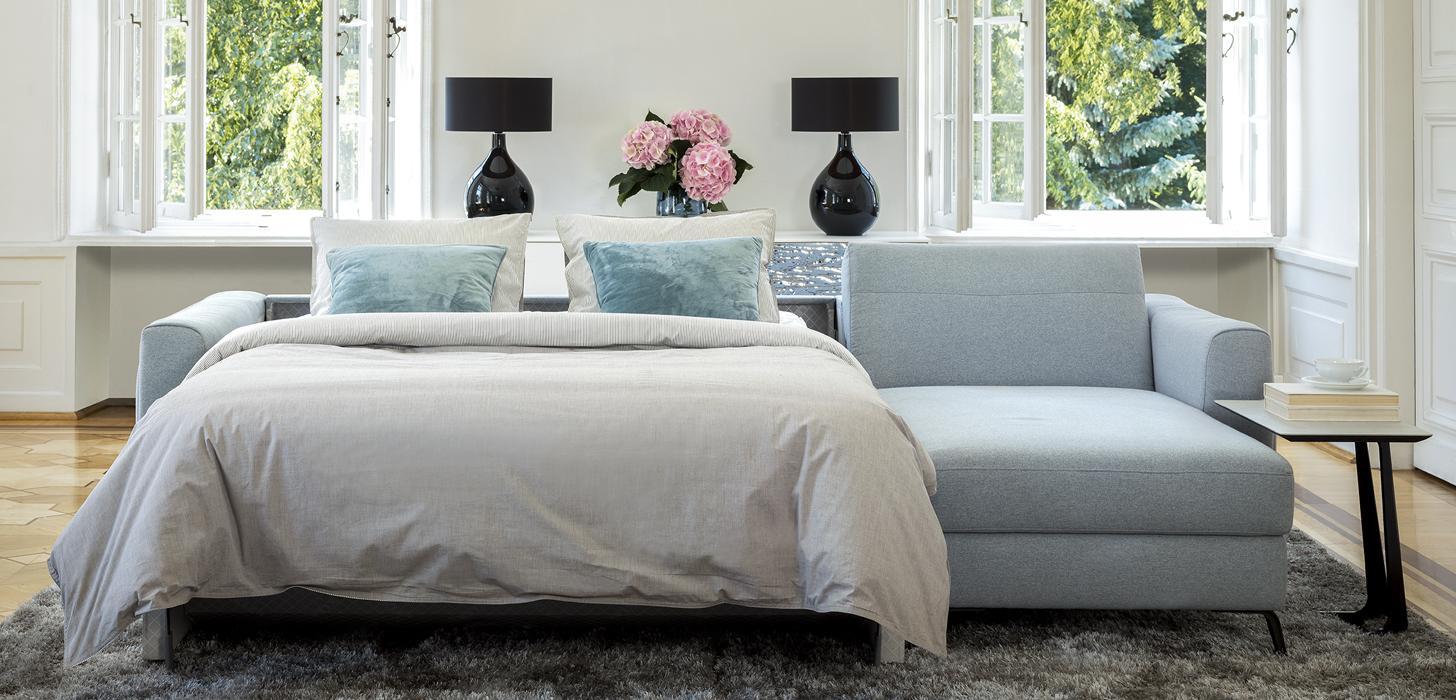 Narożnik Bolero z oferty Kler z rozłożonym łóżkiem, poduszkami i pościelą.