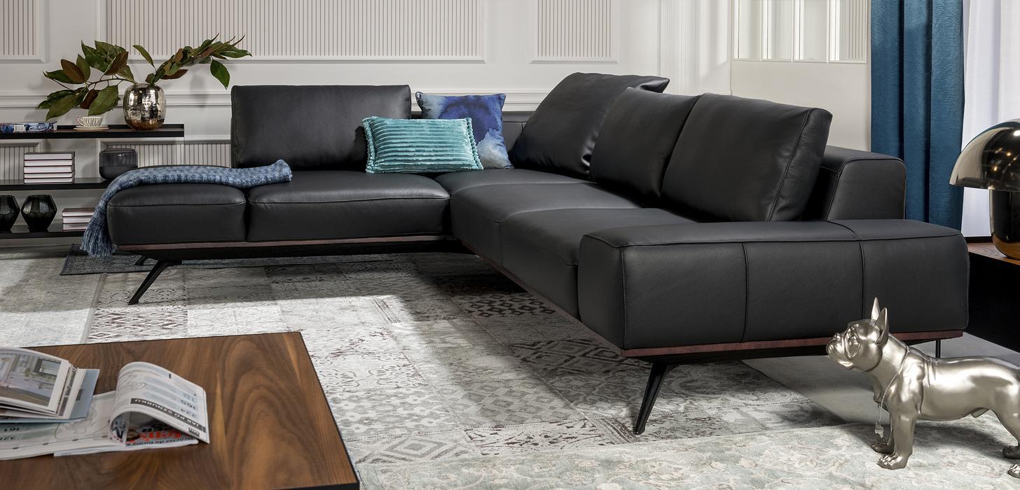 Narożnik Kler Figaro Uno - czarna skóra, dekoracyjna drewniana listwa i eleganckie czarne nóżki.