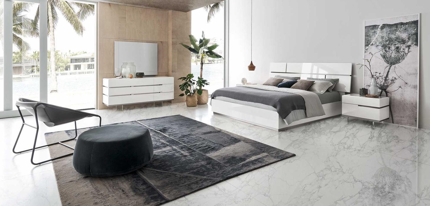 Łóżko z imponującym wezgłowiem, stolik nocny, kredens w kolorach białych, a także prostokątne lustro z kolekcji Artemide z oferty Kler.