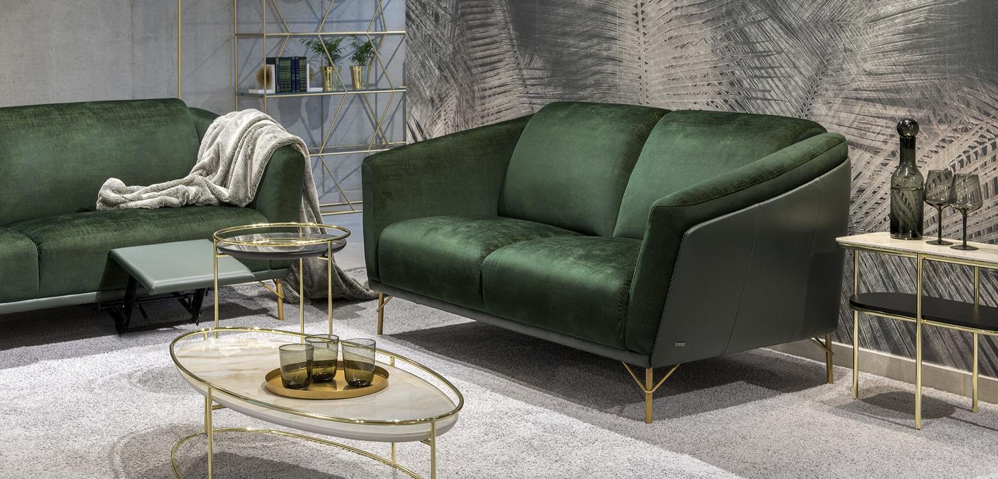 Dwuosobowa, zielona sofa Gondoliere firmy Kler ze złotymi nóżkami.Obok stolik w złotym kolorze.