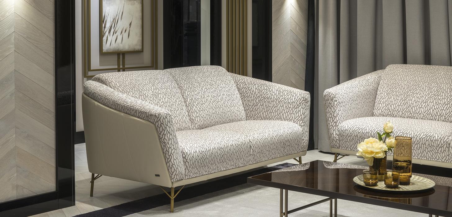 Sofa dwuosobowa Gondoliere marki Kler. Wysokie złote nóżki, beżowa skóra, jasna, wzorzysta tkanina.