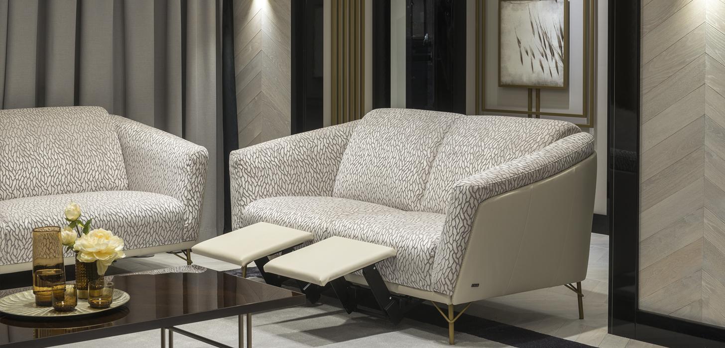 Dwuosobowa sofa Kler Gondoliere, na wysokich złotych nóżkach umieszczona w eleganckim salonie.